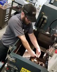 A machinist working with a Wire EDM machine at Norfolk Specialties in Norfolk, Nebraska.